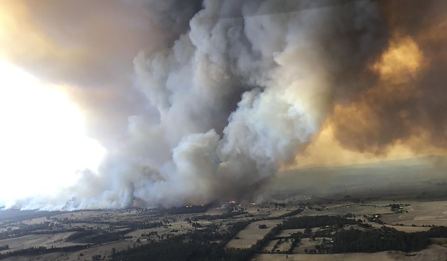 In this Monday, Dec. 30, 2019, aerial photo, wildfires rage under plumes of smoke in Bairnsdale, Australia. Thousands of tourists fled Australia's wildfire-ravaged eastern coast Thursday ahead of worsening conditions as the military started to evacuate people trapped on the shore further south. (Glen Morey via AP)