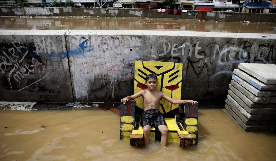 A young boy sits on a chair in a flooded neighborhood in Jakarta, Indonesia, Thursday, Jan. 2, 2020. Severe flooding in the capital as residents celebrated the new year has killed scores of people and displaced tens of thousands, the country's disaster management agency said. (AP Photo/Dita Alangkara)