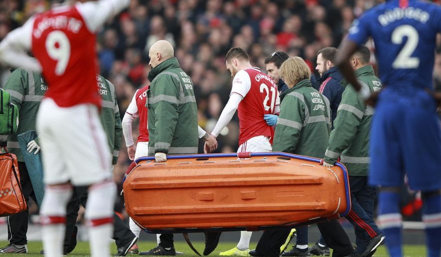 Arsenal's Calum Chambers leaves the pitch after being injured during the English Premier League soccer match between Arsenal and Chelsea, at the Emirates Stadium in London, Sunday, Dec. 29, 2019. (AP Photo/Ian Walton)