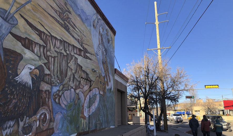 """A piece of the """"Multi-Cultural"""" mural whose creation was headed by artist Gilberto Guzman is seen in Santa Fe, N.M., on Tuesday, Dec. 31, 2019. The iconic Chicano mural painted by Mexican-American artists is scheduled for destruction in 2020 to make way for a new contemporary museum, generating a debate about gentrification and whose culture state and city officials are seeking to preserve. (AP Photo/Morgan Lee)"""