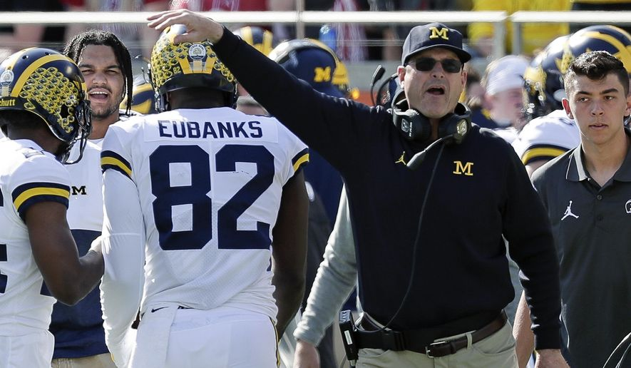 Michigan head coach Jim Harbaugh, right, congratulates tight end Nick Eubanks (82) after he caught a 7-yard touchdown pass against Alabama during the first half of the Citrus Bowl NCAA college football game, Wednesday, Jan. 1, 2020, in Orlando, Fla. (AP Photo/John Raoux)