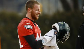 Philadelphia Eagles quarterback Carson Wentz wipes down his helmet at the NFL football team's practice facility in Philadelphia, Thursday, Jan. 2, 2020. The Seattle Seahawks travel to Philadelphia to play the Eagles in an NFC wild-card matchup on Sunday. (AP Photo/Matt Rourke)