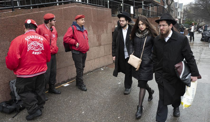Members of the Guardian Angels, left, a volunteer safety patrol organization, stand in front of the Chabad Lubavitch World Headquarters, Monday, Dec. 30, 2019 in the Brooklyn borough of New York. The Guardian Angels and police have increased patrols in the Crown Heights neighborhood following an anti-Semitic attack on a Hanukkah celebration in Monsey, N.Y. (AP Photo/Mark Lennihan)
