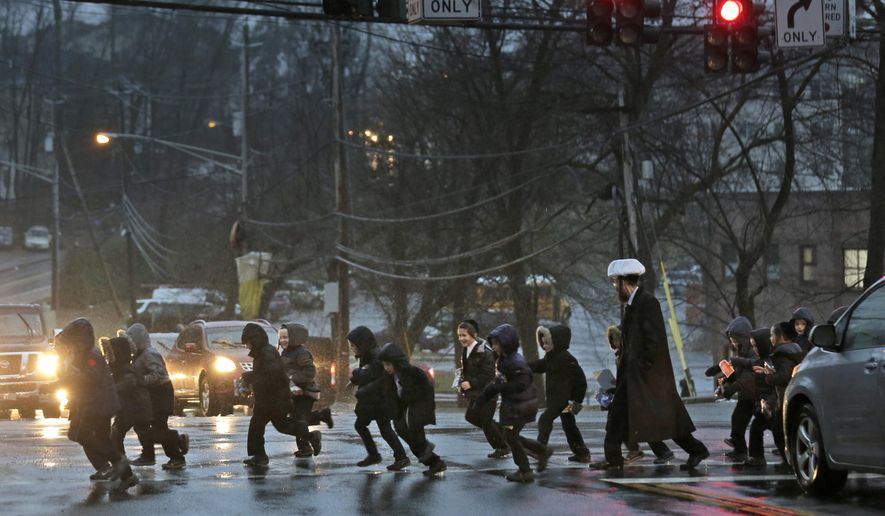 In this Monday, Dec. 30, 2019, photo, a group of orthodox Jewish children cross the street in Monsey, N.Y. With the rapid expansion of Orthodox communities outside New York City has come civic sparring, and some fear the recent violence in the area may be an outgrowth of that conflict. (AP Photo/Seth Wenig)