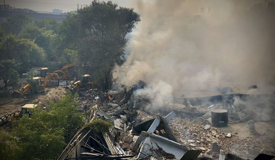 Smoke rises after a factory caught fire and collapsed in Peera Garhi area in western New Delhi, India, Thursday, Jan. 2, 2020. Several people, including some fire officials were injured. (AP Photo/Manish Swarup)