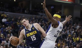 Denver Nuggets' Nikola Jokic (15) goes to the basket against Indiana Pacers' Myles Turner (33) during the first half of an NBA basketball game Thursday, Jan. 2, 2020, in Indianapolis. (AP Photo/Darron Cummings)