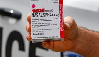 FILE - In this Thursday, Sept. 12, 2019 file photo, a police officer holds a box of Narcan, a drug used to treat opioid overdoses, that the department officers carry in their patrol vehicles in Jackson Township, Butler County, Pa. More companies could begin making the easy-to-use version of the medication under a deal announced Thursday, Jan. 2, 2020 by New York's attorney general. (AP Photo/Keith Srakocic)