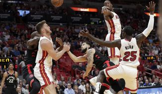 Toronto Raptors guard Fred VanVleet, center, drives to the basket as Miami Heat forward Meyers Leonard, left, center Bam Adebayo, center, and guard Kendrick Nunn (25) defend during the first half of an NBA basketball game, Thursday, Jan. 2, 2020, in Miami. (AP Photo/Lynne Sladky)