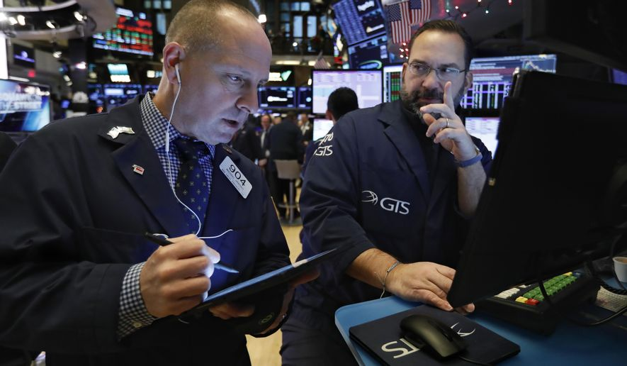 FILE - In this Dec. 11, 2019, file photo trader Michael Urkonis, left, and specialist Anthony Matesic work on the floor of the New York Stock Exchange. The U.S. stock market opens at 9:30 a.m. EST on Friday, Jan. 3, 2020. (AP Photo/Richard Drew, File)