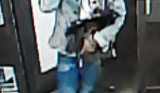 This image provided by the Lafourche Parish Sheriff Office shows a suspect entering a convenience store in Galliano, La. Louisiana authorities are trying to identify a man who left apparent designer bags holding drugs, a gun, cash and a digital scale in a convenience store. The man went into the store early Thursday, Jan. 2, 2020 and put the apparent Louis Vuitton and Gucci bags on a chair, according to a news release. (Lafourche Parish Sheriff Office via AP)