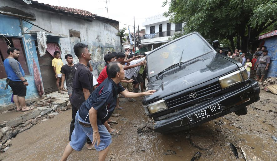 Residents move the wreckage of cars that were swept away by flood in Bekasi, West Java, Indonesia, Friday, Jan. 3, 2020.Severe flooding in greater Jakarta has killed scores of people and displaced tens of thousands others, the country's disaster management agency said. (AP Photo/Achmad Ibrahim)