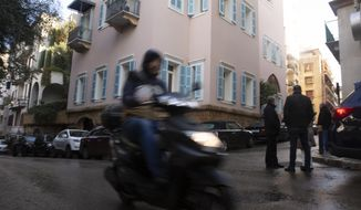 A motorbike passes the house of ex-Nissan chief Carlos Ghosn in Beirut, Lebanon, Friday, Jan. 3, 2020. The former Nissan Motor Co. Chairman fled Japan this week while awaiting trial on financial misconduct charges and appeared in Lebanon. (AP Photo/Maya Alleruzzo)