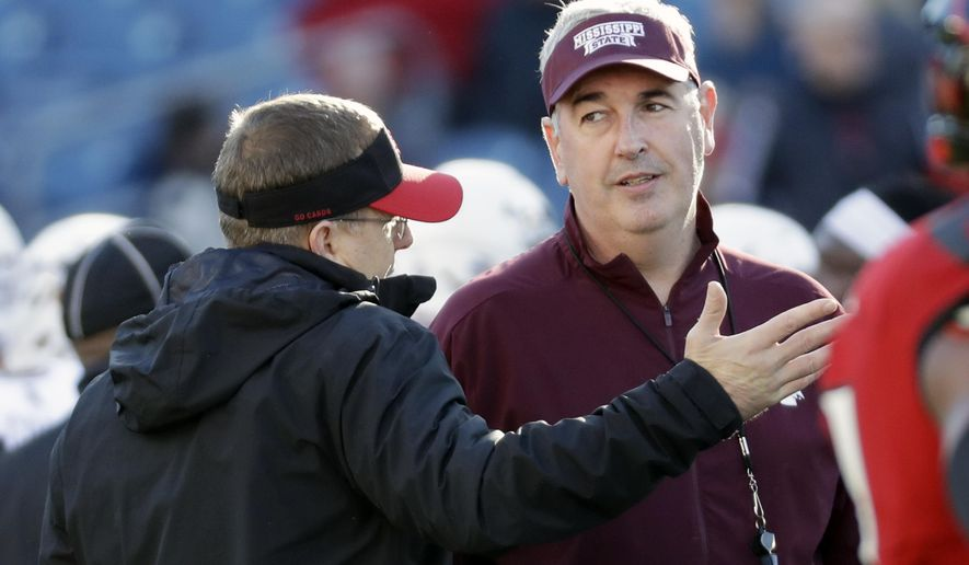 Mississippi State head coach Joe Moorhead, right, talks with Louisville head coach Scott Satterfield before the Music City Bowl NCAA college football game Monday, Dec. 30, 2019, in Nashville, Tenn. (AP Photo/Mark Humphrey)