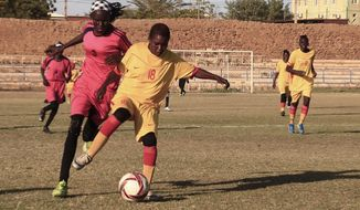 In this Wednesday, Dec. 11, 2019 photo, Sudanese al-Difaa, in pink, and al-Sumood women teams play in Omdurman, Khartoum's twin city, Sudan. The women's soccer league has become a field of contention as Sudan grapples with the transition from three decades of authoritarian rule that espoused a strict interpretation of Islamic Shariah law. (AP Photo)