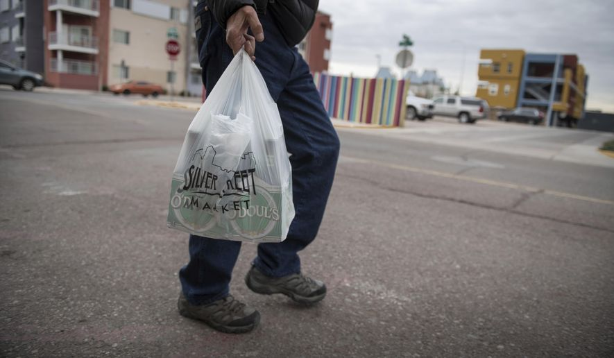 In this Jan. 10, 2019, file photo a shopper carries groceries in a plastic bag after shopping at the Silver Street Market in downtown Albuquerque, N.M. Businesses in New Mexico's largest metropolitan area are preparing for rules that will take effect with the start of the new year that call for banning plastic bags. (Roberto E. Rosales/The Albuquerque Journal via AP, File)