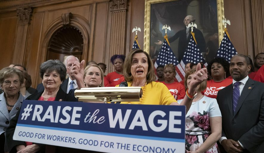 FILE - In this July 18, 2019, file photo speaker of the House Nancy Pelosi, D-Calif., joins fellow Democrats and activists seeking better pay as the House approved legislation to raise the federal minimum wage for the first time in a decade _ to $15 an hour, at the Capitol in Washington. As of Jan. 1, 2020, there are higher minimum wages in a quarter of the states, and new federal overtime rules. (AP Photo/J. Scott Applewhite, File)