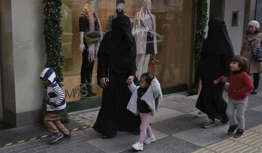FILE - In this Dec. 3, 2019 file photo, refugee women walk with their children on a main street, in Ankara, Turkey.  Turkey currently host about four million Syrian refugees and faces a possible new refugee influx from Syria, where Russian and Syrian government forces have redoubled their offensive in Idlib, the last rebel-held province.(AP Photo/Burhan Ozbilici, FILE)