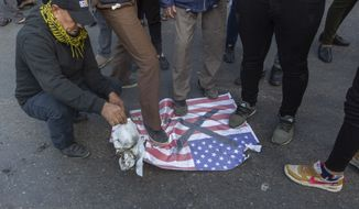 """Mourners step over a U.S. flags before burning it during the funeral of Iran's top general Qassem Soleimani and Abu Mahdi al-Muhandis, deputy commander of Iran-backed militias in Iraq known as the Popular Mobilization Forces, in Baghdad, Iraq, Saturday, Jan. 4, 2020. Thousands of mourners chanting """"America is the Great Satan"""" marched in a funeral procession Saturday through Baghdad for Iran's top general and Iraqi militant leaders, who were killed in a U.S. airstrike. (AP Photo/Nasser Nasser)"""