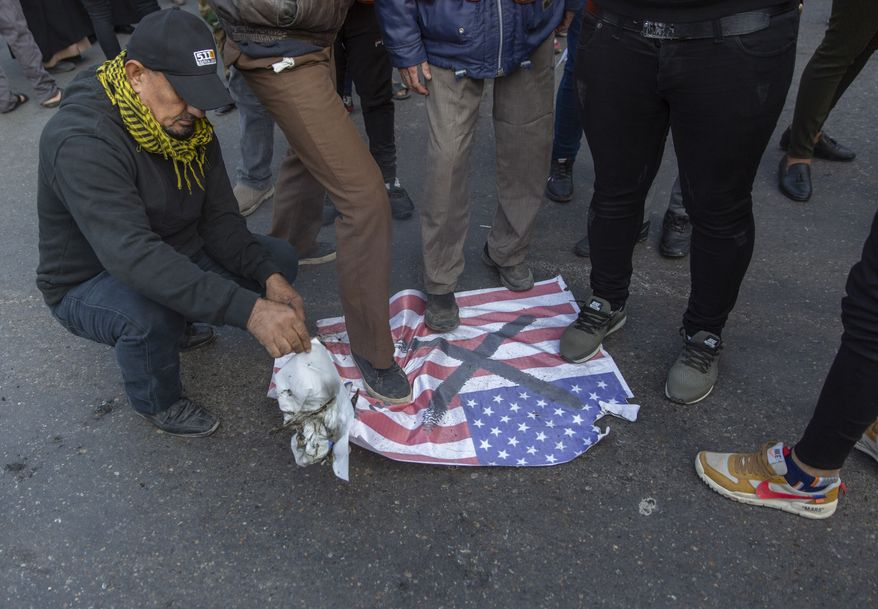 "Mourners step over a U.S. flags before burning it during the funeral of Iran's top general Qassem Soleimani and Abu Mahdi al-Muhandis, deputy commander of Iran-backed militias in Iraq known as the Popular Mobilization Forces, in Baghdad, Iraq, Saturday, Jan. 4, 2020. Thousands of mourners chanting ""America is the Great Satan"" marched in a funeral procession Saturday through Baghdad for Iran's top general and Iraqi militant leaders, who were killed in a U.S. airstrike. (AP Photo/Nasser Nasser)"
