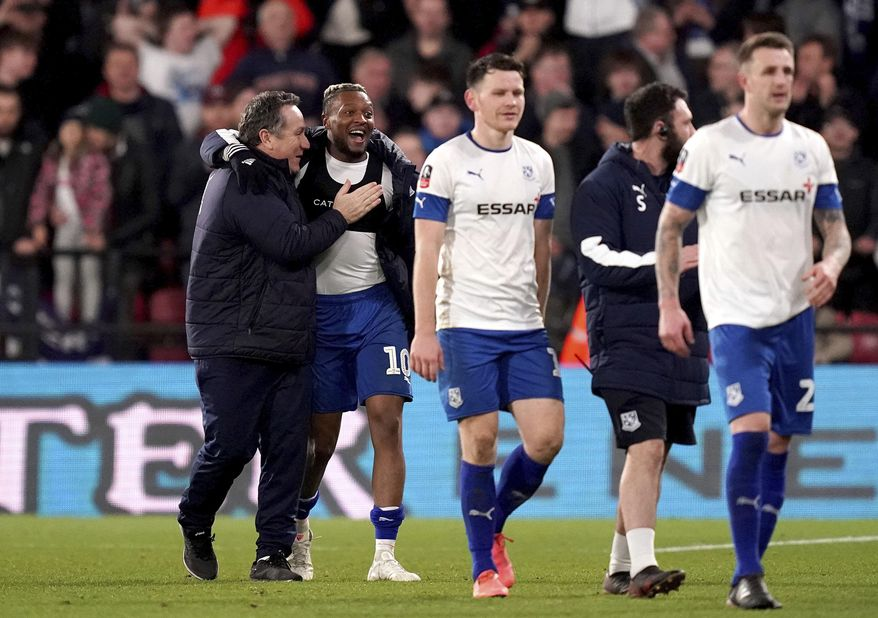 Tranmere Rovers manager Micky Mellon, left, celebrates with Morgan Ferrier after his side earn a replay with a draw following the English FA Cup third round soccer match between Watford and Tranmere Rovers at Vicarage Road, Watford, England, Saturday, Jan. 4, 2020. (John Walton/PA via AP)