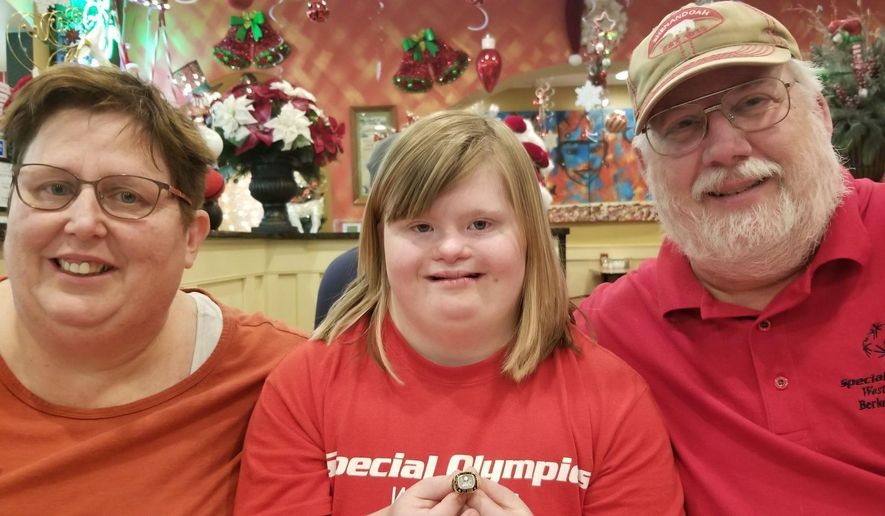 In this Dec. 28, 2019 photo, Peggy Molnar, center, of Martinsburg, W.Va., poses with her parents, Ginnie Molnar and Ken Dellinger in Martinsburg, W.Va. Peggy Molnar was chosen as one of two 2019-20 Big 12 Special Olympics Athletes of the Year, ( Jenni Vincent/The Herald-Mail via AP)