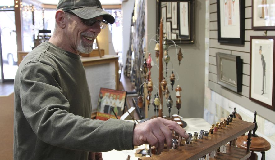 Tom Schroeder goes through the range of unique pens on display and for sale at The Villager in Beloit in this Dec. 14, 2019 photo. Schroeder fell in love with woodworking when he was a boy, and now he wants to share his passion with the Stateline Area and beyond. (Austin Montgomery/The Beloit Daily News via AP)