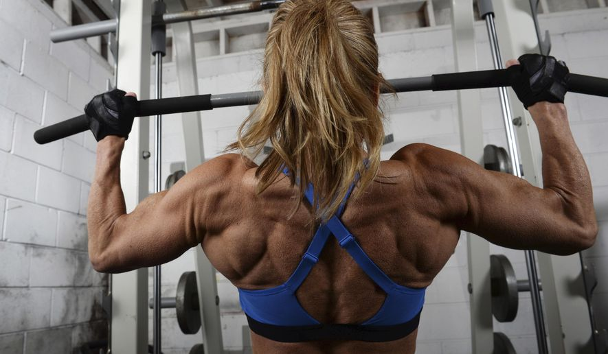 In this Dec. 17, 2019, photo, Dawn Shafer Forbes works out in her home gym in Arden Hills, Minn. Forbes, recently named World Champion of Pro Women's Bodybuilding at the 2019 International Pro Elite World Championships, is at 54, the oldest competitor ever to win the title. (Scott Takushi/Pioneer Press via AP)