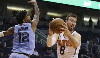 Phoenix Suns forward Frank Kaminsky (8) grabs a rebound in front of Memphis Grizzlies guard Ja Morant (12) during the second half of an NBA basketball game, Wednesday, Dec. 11, 2019, in Phoenix. The Grizzlies defeated the Suns 115-108. (AP Photo/Ross D. Franklin)