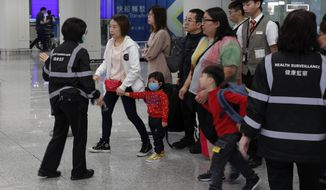 "Health surveillance officer use device to check temperature of passengers before the immigration counters at International airport in Hong Kong, Saturday, Jan. 4, 2020. Hong Kong authorities activated a newly created ""serious response"" level Saturday as fears spread about a mysterious infectious disease that may have been brought back by visitors to a mainland Chinese city. (AP Photo/Andy Wong)"