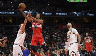Washington Wizards guard Ish Smith (14) goes to the basket between Denver Nuggets guard Jamal Murray (27) and center Nikola Jokic, left, during the second half of an NBA basketball game, Saturday, Jan. 4, 2020, in Washington. The Wizards won 128-114. (AP Photo/Nick Wass)