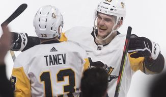 Pittsburgh Penguins' Brandon Tanev (13) celebrates with teammate Teddy Blueger after scoring during overtime in an NHL hockey game against the Montreal Canadiens, Saturday, Jan. 4, 2020 in Montreal. (Graham Hughes/The Canadian Press via AP)