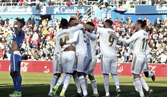 Real Madrid's Raphael Varane, third left, celebrates after scoring his side's opening goal during a Spanish La Liga soccer match between Getafe and Real Madrid at the Coliseum Alfonso Perez stadium in Getafe, Spain, Saturday, Jan. 4, 2020. (AP Photo/Paul White)