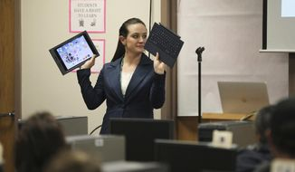 In this Dec. 18, 2019, photo, Renda Fisk, Technology Integration Coordinator for the Flagstaff Unified School District, holds up an iPad and a keyboard during an open house at Sinagua Middle School in Flagstaff, Ariz. The Flagstaff school district is about to begin providing all of its students with an iPad, a loan program that starts this month with middle and high school students at the beginning of the 2020 spring semester and continues with elementary school students at the start of the next school year. (Jake Bacon/Arizona Daily Sun via AP)