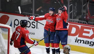 Washington Capitals center Lars Eller (20), of Denmark, celebrates his game-winning goal in overtime of an NHL hockey game with defenseman John Carlson (74) and right wing T.J. Oshie (77) against the San Jose Sharks, Sunday, Jan. 5, 2020, in Washington. The Capitals won 5-4 in overtime. (AP Photo/Nick Wass)
