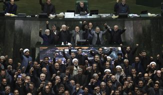 Iranian lawmakers chant anti-American and anti-Israeli slogans to protest against the U.S. killing of Iranian top general Qassem Soleimani, at the start of an open session of parliament in Tehran, Iran, Sunday, Jan. 5, 2020. Soleimani's death Friday in Iraq further heightens tensions between Tehran and Washington after months of trading attacks and threats that put the wider Middle East on edge. (Mohammad Hassanzadeh/Tasnim News Agency via AP)