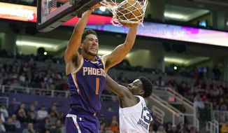 CORRECTS TO SAY THE GRIZZLIES WON, NOT THE SUN -  Phoenix Suns guard Devin Booker (1) dunks over Memphis Grizzlies forward Jaren Jackson Jr. in the second half during an NBA basketball game, Sunday, Jan. 5, 2020, in Phoenix. The Grizzlies won 121-114. (AP Photo/Rick Scuteri)
