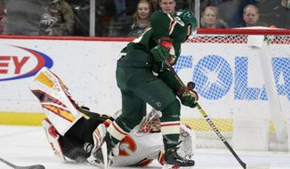 Calgary Flames goalie David Rittich (33) makes a stop on Minnesota Wild left wing Kevin Fiala in the third period during an NHL hockey game Sunday, Jan. 5, 2020, in St. Paul, Minn. The Flames defeated the Wild 5-4 in the shoot out. (AP Photo/Andy Clayton-King)