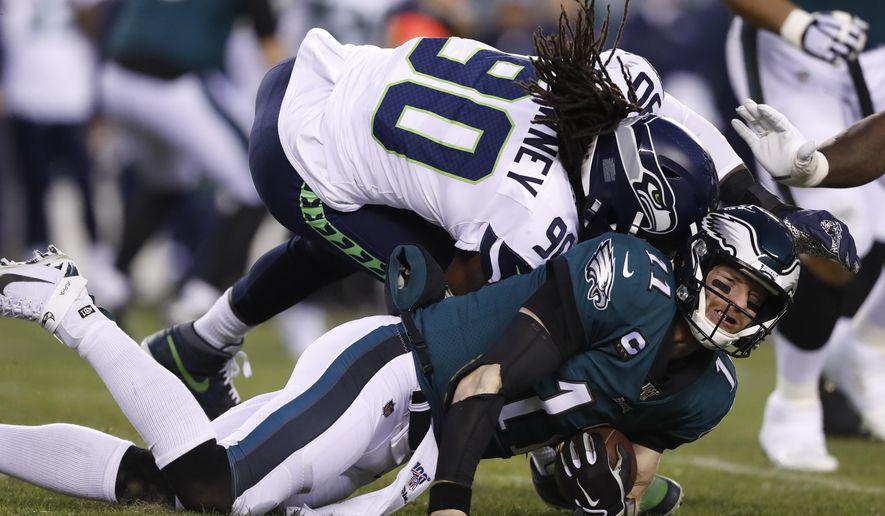 Seattle Seahawks' Jadeveon Clowney (90) hits Philadelphia Eagles' Carson Wentz (11) during the first half of an NFL wild-card playoff football game, Sunday, Jan. 5, 2020, in Philadelphia. (AP Photo/Julio Cortez)