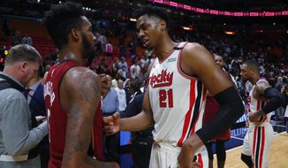 Portland Trail Blazers center Hassan Whiteside (21) and Miami Heat forward Derrick Jones Jr. (5) talk after an NBA basketball game, Sunday, Jan. 5, 2020, in Miami. The Heat defeated the Trail Blazers 122-111. (AP Photo/Wilfredo Lee)