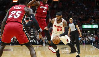 Portland Trail Blazers forward Carmelo Anthony (00) drives to the basket against Miami Heat guard Kendrick Nunn (25) and center Bam Adebayo (13) during the first half of an NBA basketball game, Sunday, Jan. 5, 2020, in Miami. (AP Photo/Wilfredo Lee)