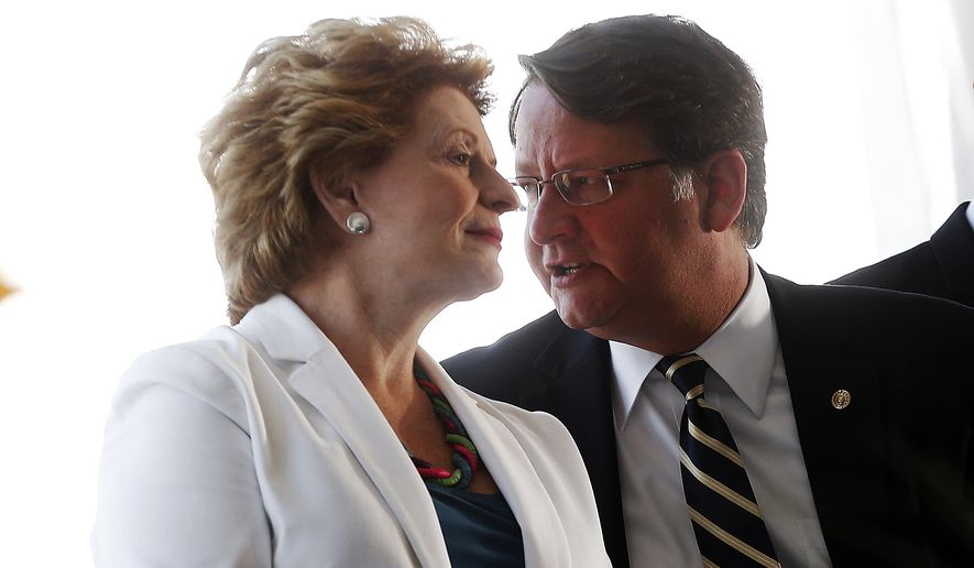 Sen. Debbie Stabenow, D-Mich., and Sen. Gary Peters, D-Mich., talk at the opening of Mcity Monday, July 20, 2015 in Ann Arbor, Mich. The University of Michigan officially opened the simulated city that will be used to test driverless and connected vehicles. The 32-acre site on the university's Ann Arbor campus has building facades, a roundabout, brick and gravel roads and other driving features.(AP Photo/Paul Sancya)