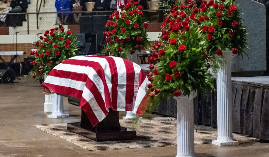 "The casket sits, under a U.S. Flag, flanked by rose bushes, during the memorial service for slain Lowndes County Sheriff ""Big John"" Williams, Monday, Dec. 2, 2019, in Montgomery, Ala. (AP Photo/Vasha Hunt)"