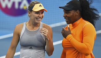 Denmark's Caroline Wozniacki, left, and Untied States' Serena Williams talk during their first round doubles match against Japan's Nao Hibino and Makoto Ninomiya at the ASB Classic in Auckland, New Zealand, Monday, Jan 6, 2020. (Chris Symes/Photosport via AP)