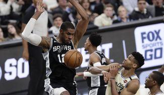 San Antonio Spurs center LaMarcus Aldridge (12) scores over Milwaukee Bucks forward Thanasis Antetokounmpo, second from right, during the second half of an NBA basketball game in San Antonio, Monday, Jan. 6, 2020. (AP Photo/Eric Gay)