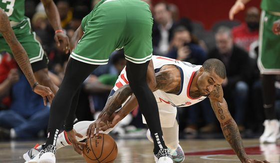 Washington Wizards guard Gary Payton II, right, and Boston Celtics guard Jaylen Brown, left, battle for the ball during the first half of an NBA basketball game, Monday, Jan. 6, 2020, in Washington. (AP Photo/Nick Wass)