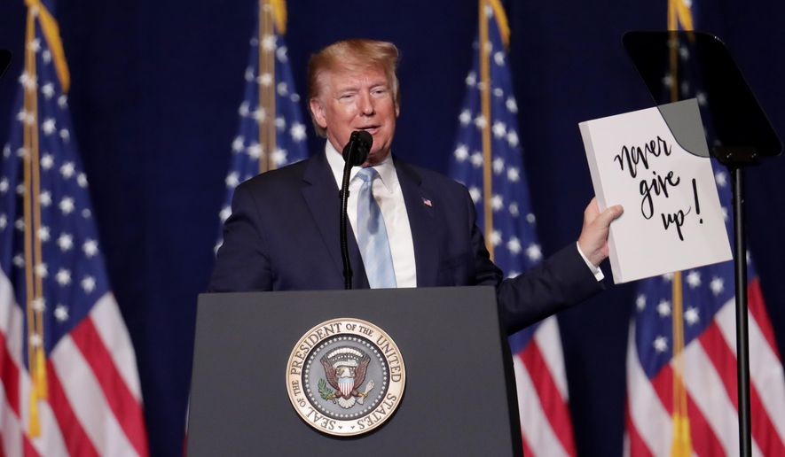 President Donald Trump holds up a sign given to him by a supporter during a rally for evangelical supporters at the King Jesus International Ministry, Friday, Jan. 3, 2020, in Miami. (AP Photo/Lynne Sladky)