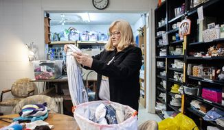 Donna Anderson removes a shirt from a bag of donated clothing Tuesday, Dec. 10, 2019, at Acts of Kindness in Janesville, Wis. The local nonprofit was founded in 2008 and depends on private donations for survival. Anderson says the organization is seeing more people who are struggling financially.  (Angela Major/The Janesville Gazette via AP)