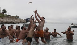 Pilgrims jump to catch the cross during a water blessing ceremony marking the Epiphany celebrations at Piraeus suburb, near Athens, on Monday, Jan. 6, 2020.  Similar ceremonies marking Epiphany were held across Greece on river banks, seafronts and lakes, where Orthodox priests throw a cross into the water and swimmers race to retrieve it. (AP Photo/Thanassis Stavrakis)