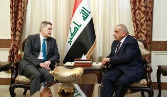 A photo released by the Iraqi Prime Minister Media Office, shows Iraqi acting Prime Minister Adil Abdul-Mahdi, right, meeting with U.S. Ambassador to Iraq Matthew Tueller at the prime minister's office, in Baghdad, Iraq, Monday, Jan. 6, 2020. (Iraqi Prime Minister Media Office, via AP)