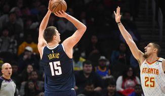 Denver Nuggets center Nikola Jokic (15) shoots as Atlanta Hawks center Alex Len (25) defends during an NBA basketball game Monday, Jan. 6, 2020, in Atlanta. (AP Photo/John Amis)